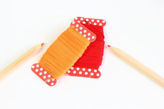 オレンジと赤の糸と色鉛筆