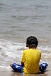 波打ち際に座る少年