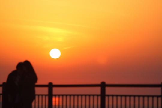 夕日と二人の人影