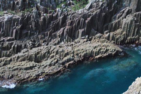 青く澄んだ海と柱状節理の岩