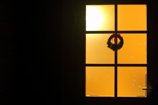 明かりの漏れたガラス扉とクリスマスリース