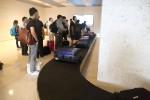 手荷物レーンで荷物を待つ人々