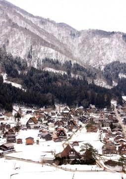 控えめに雪をいただく白川郷と冬枯れの里山