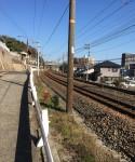 早春の雲ひとつない青空と線路沿いの道